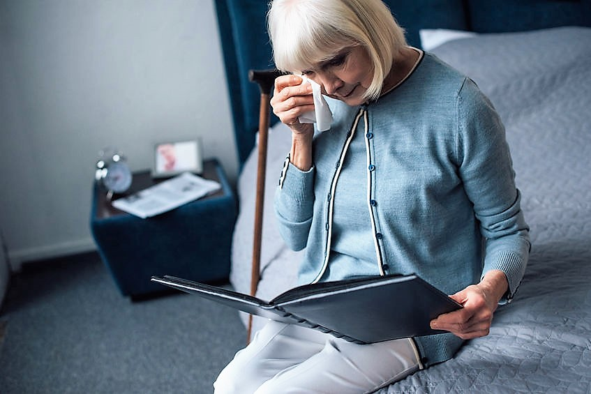 Grandmother with tears looking at photo album